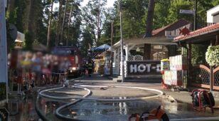 Smażalnia ryb w ogniu. Wokół zaparkowane auta i wczasowicze.