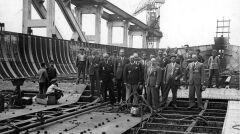 Narodziny Batorego we włoskiej stoczni. Oficjele stoją na dnie statku a w tle widać początki burt