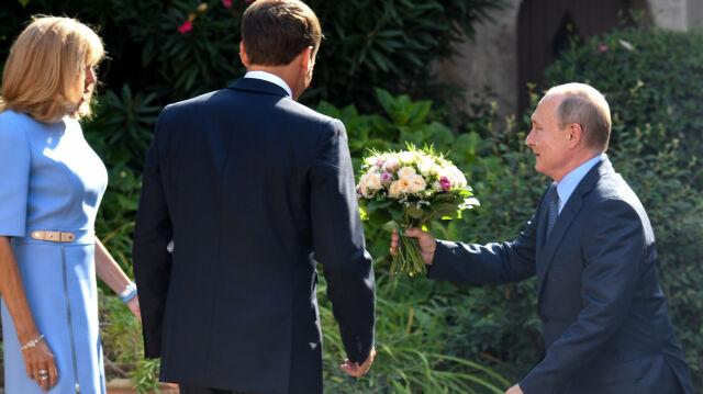 Prezydent Rosji Władimir Putin wręcza kwiaty żonie prezydenta Francji Brigitte Macron