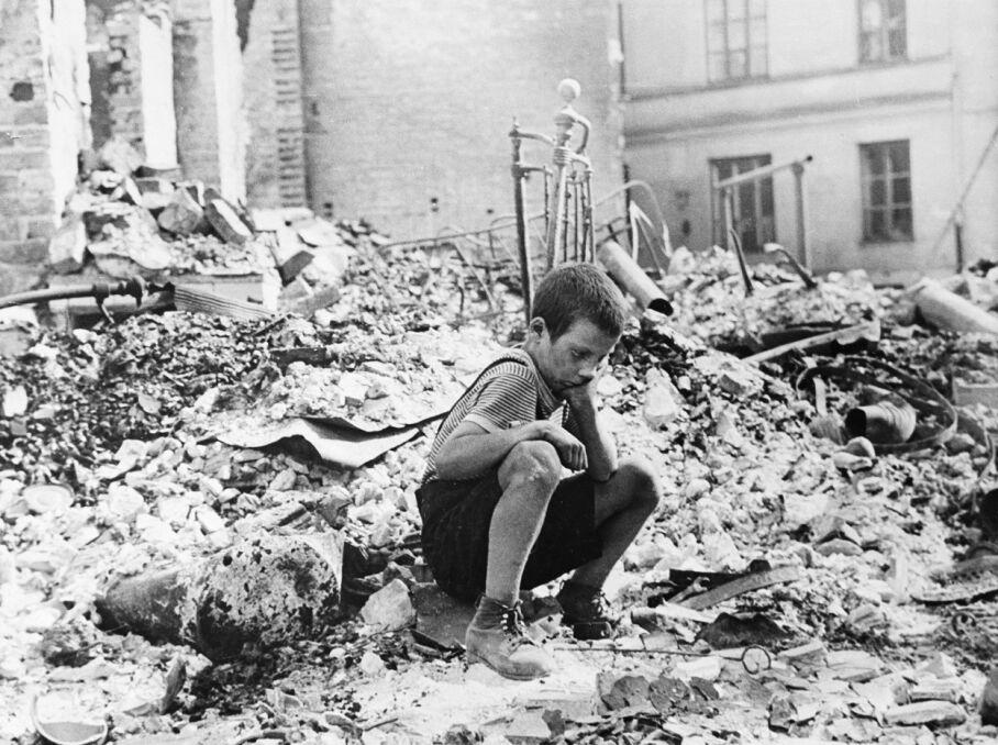 Chłopiec na ruinach zbombardowanego budynku
