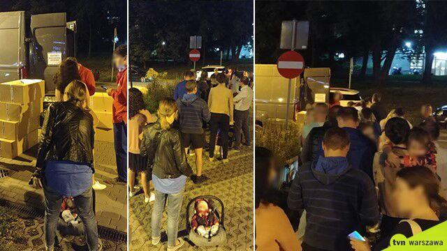Tłum rodziców na parkingu.  Miejskie wyprawki rozdawane z busa
