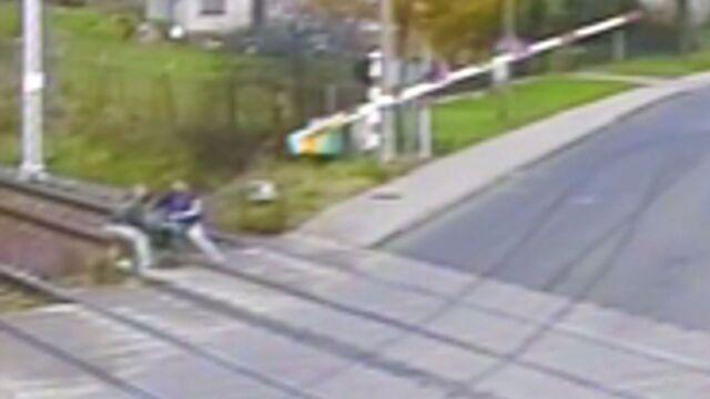 Mężczyzna leży na torach, rogatki opadają. Policjanci i kierowca ruszyli z pomocą