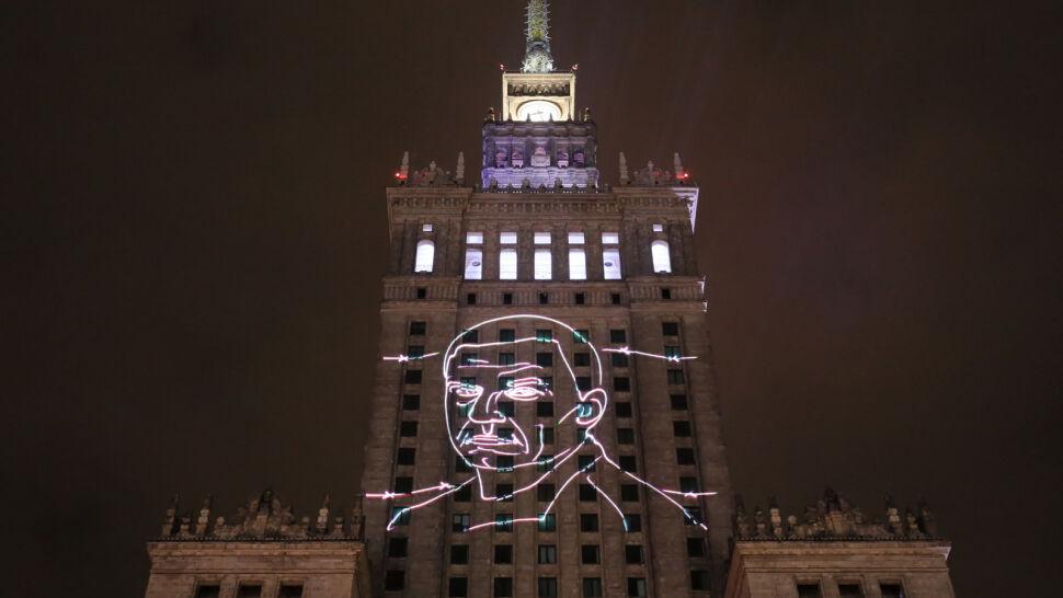 Wiec poparcia dla Andrzeja Poczobuta przed PKiN. Wizerunek uwięzionego dziennikarza wyświetlony na fasadzie budynku