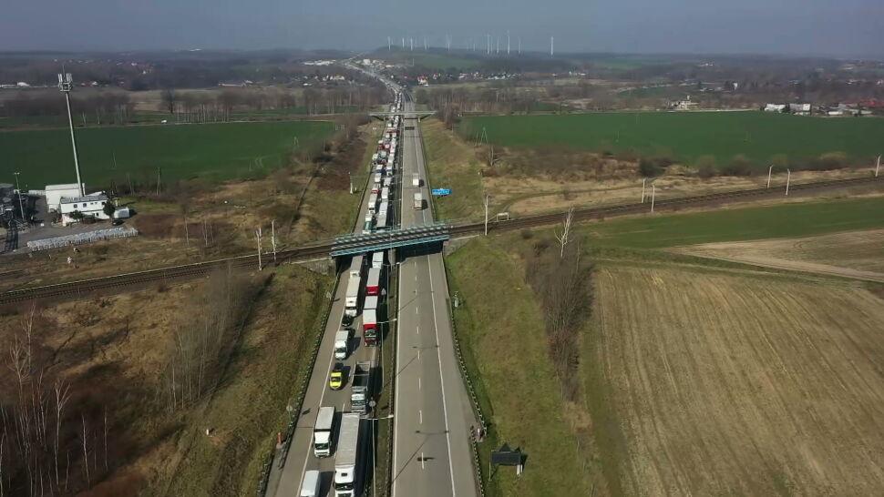 Wolontariusze rozdają wodę i jedzenie w kolejce do granicy z Polską